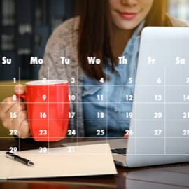 A woman drinking coffee at a desk with a transparent calendar in front.