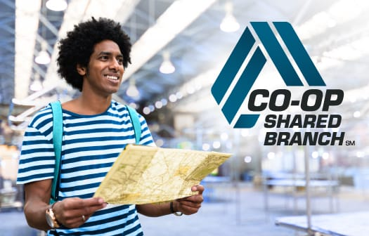 A man wearing a backpack holding a map with the CO-OP Shared Branch logo to the right