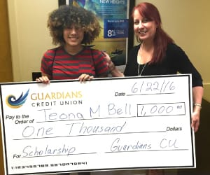 Teona Bell holding a human-sized check for $1,000