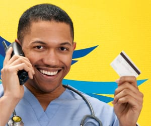 A man smiling on the telephone and holding an ATM card
