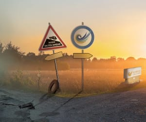 Crossroad with two signs: High Rates Ahead, Guardians Logo