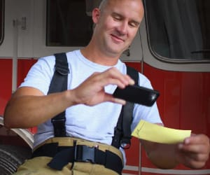 A firefighter taking a picture of a check with a smartphone.