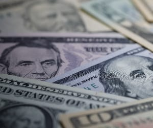 Several dollar bills spread over a flat surface.