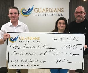 A scholarship winner holding a human sized check.
