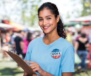 A young woman smiling and holding a clipboard with a Vote button pinned to her t-shirt.