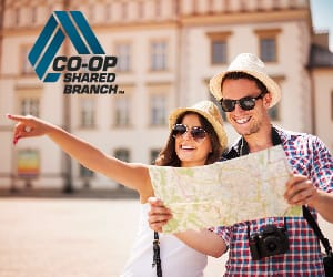 A young couple wearing sun glasses and straw hats looking at a world map.