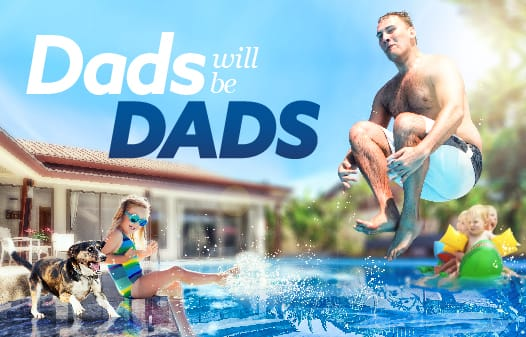 A dad jumping into a pool while his kids look and splash water.