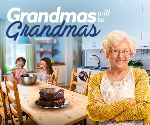 A grandmother standing at the head of a kitchen table with grandkids eating chocolate cake.