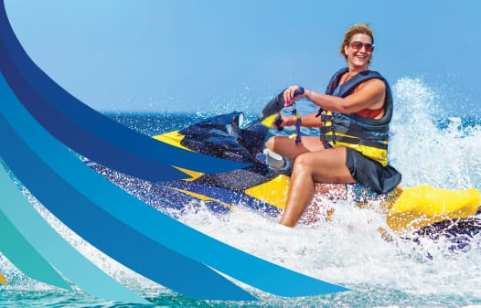 A mom driving a jetski on a sunny ocean day.