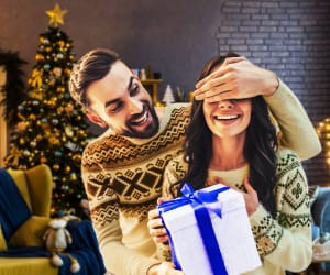 A young couple opening a holiday present in front of a christmas tree.