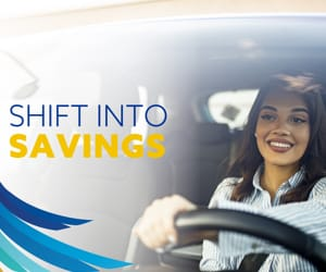 A young woman smiling while driving a car. At the top left, the words: Shift into savings.