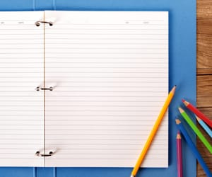 An open folder with blank ruled paper and colorful pencils laying on top of it.