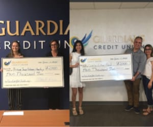 Two scholarship winners holding a human-sized check.