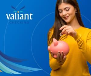 A teenage girl depositing a coin into a piggy bank.