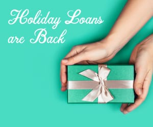 A hand holding a gift box. To the left, the words: holiday loans are back