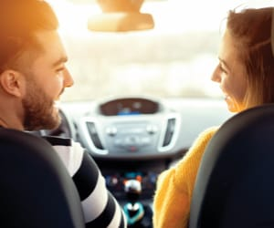An interior cabin view of a couple driving in while smiling at each other.