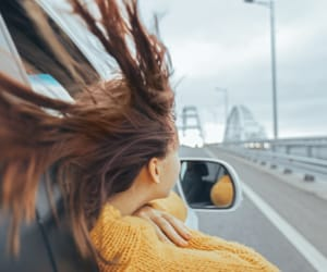 A woman hanging outside the passenger window of a car with her hair blowing in the wind.