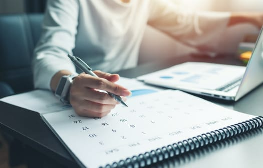 A person sitting at a desk with a calendar open.