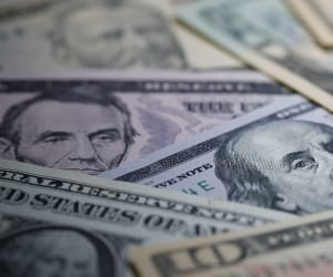 A close up of dollar bills spread over each other.