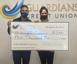 Maricarmen Torres Concepcion receiving a human sized check for $2,000.
