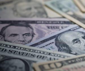 US Dollar bills spread over a table.