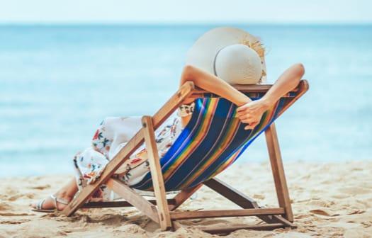 A women relaxing on a beach chair on the beach.