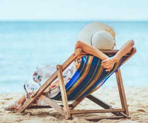A woman relaxing in a beach chair on the beach.