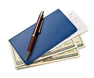A brown pen laying over a blue checkbook