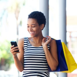 A young woman carrying shopping bags while holding a smartphone.