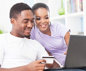 A smiling couple with one holding a credit card and the other looking at a laptop