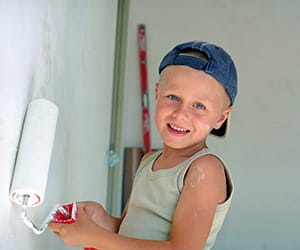 A young boy wearing a blue cap using a roller brush to paint a wall