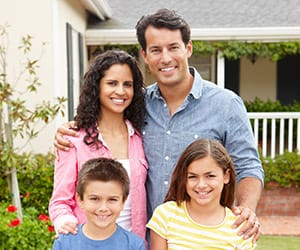 A family of two smiling and standing together on the lawn of their home
