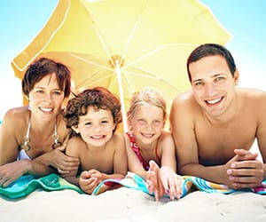 A family of two kids smiling at the beach under a yellow umbrella