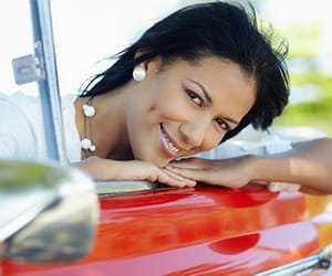 A woman smiling and sitting in a red car leaning over its door