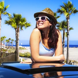 Woman smiling and wearing sunglasses while standing through the sunroof of a car
