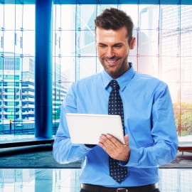 Man smiling wearing a shirt and tie looking downwards at a held tablet