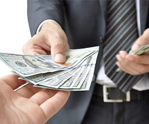 A man in a suit handing over several $100 bills