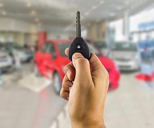 A hand holding an automobile key inside an auto delearship
