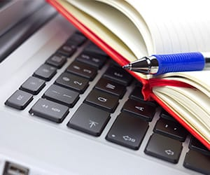 An open notebook with a blue pen on top of a laptop
