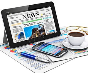 A tablet showing an online newspaper next to a coffe cup on top papers of charts and graphs