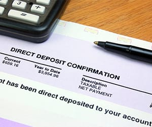 A calculator and pen on top of a Direct Deposit Confirmation document