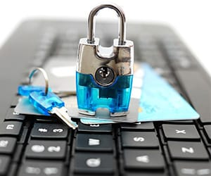 A blue lock and key on top of credit cards that are laying over a laptop
